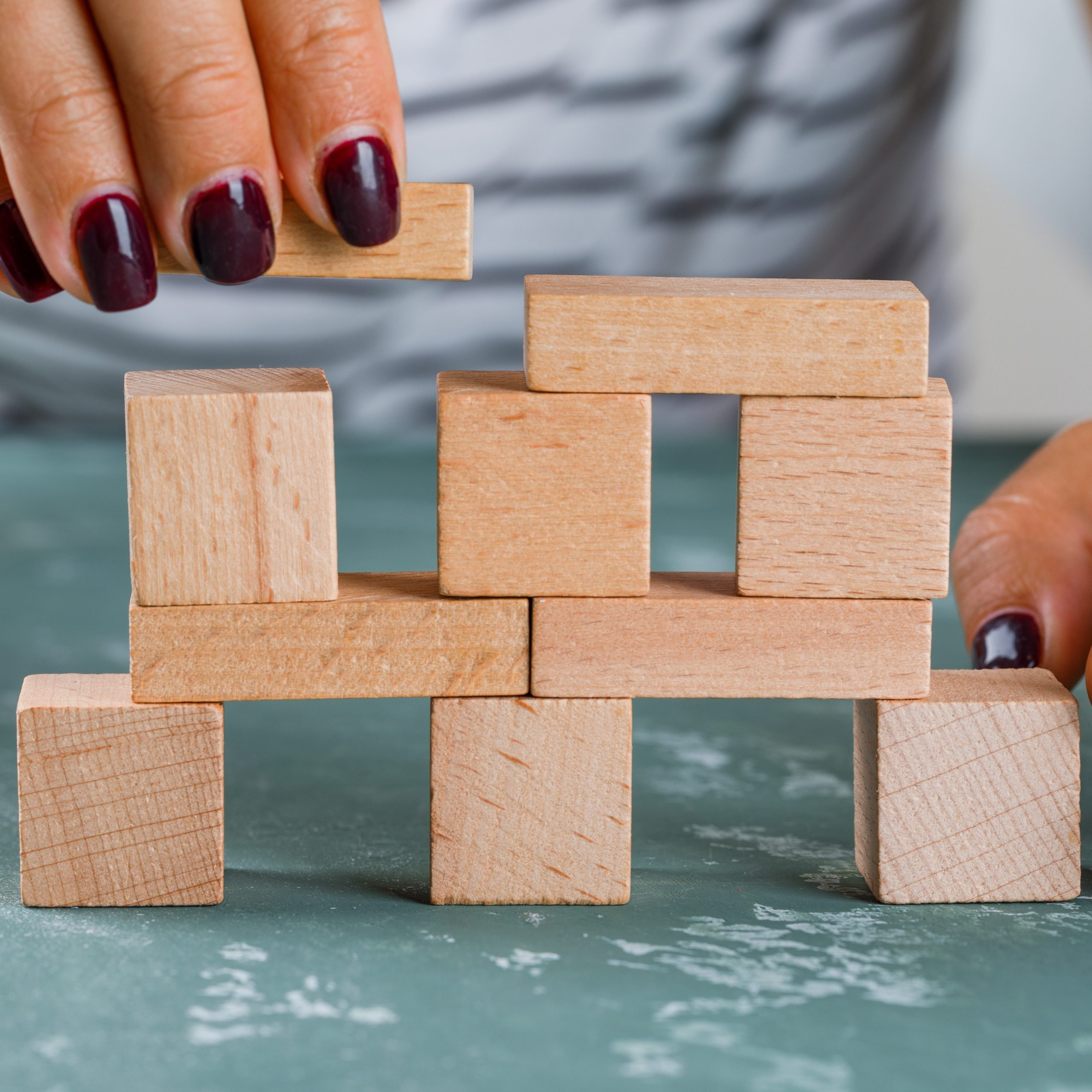 A hnad building a tower using blocks